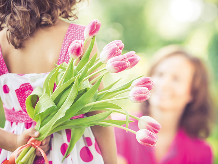 Young girl with tulips behind her back with mother blurred in the distance